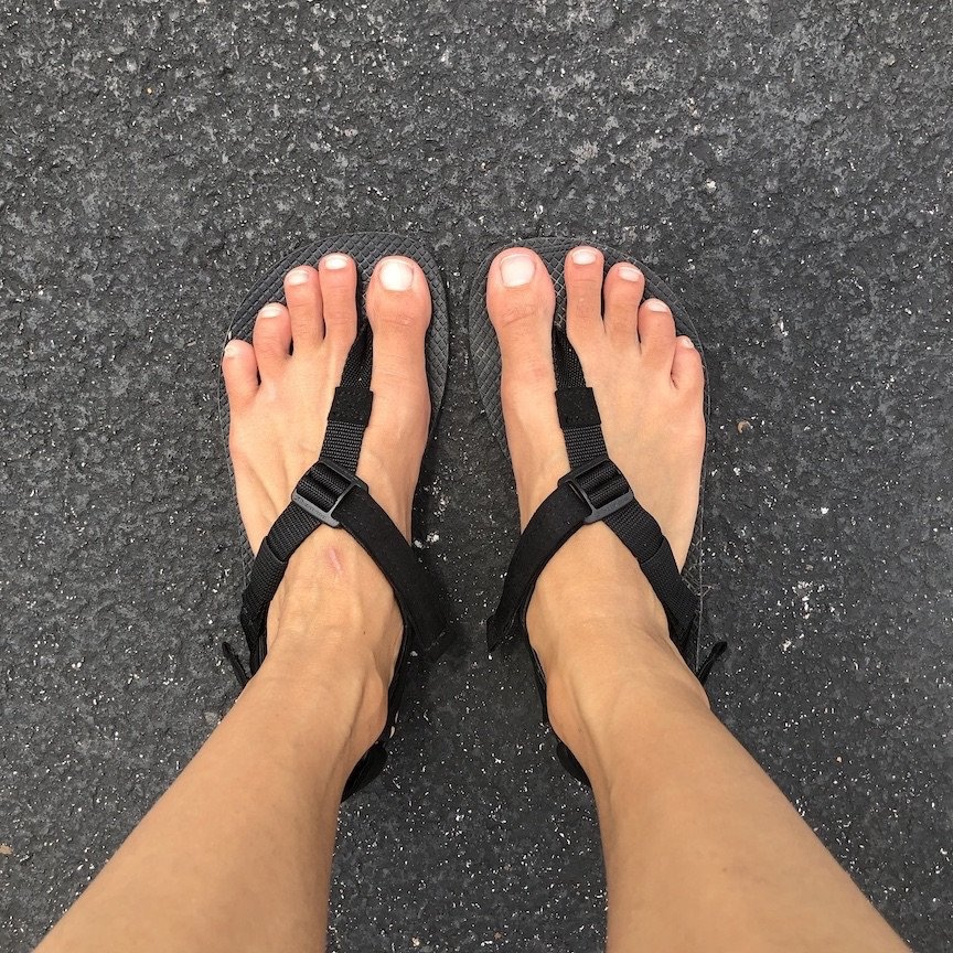 The black Shamma Warrior Sandals shown on feet without the Power Straps, top down on view on asphalt
