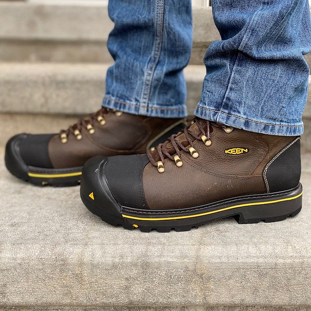 A close up of a pair of feet wearing the men's Keen Utility Boot