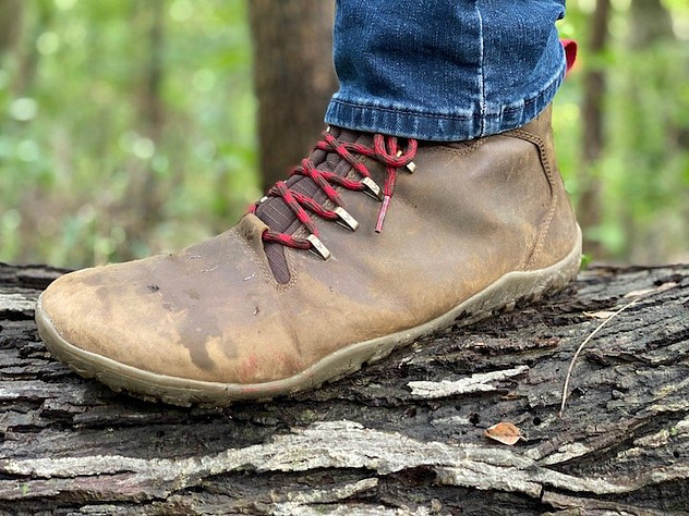 A side view of a foot wearing the Vivobarefoot Tracker barefoot hiking boot, standing on a log outdoors