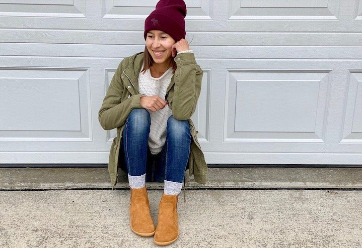 A woman sitting on the ground in front of a closed garage door wearing a coat, hat, and vivobarefoot fulham chelsea boots, smiling and looking to the side.
