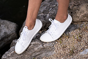 a close up view of Belenka Barefoot White Prime Sneakers on feet outside next to rocks