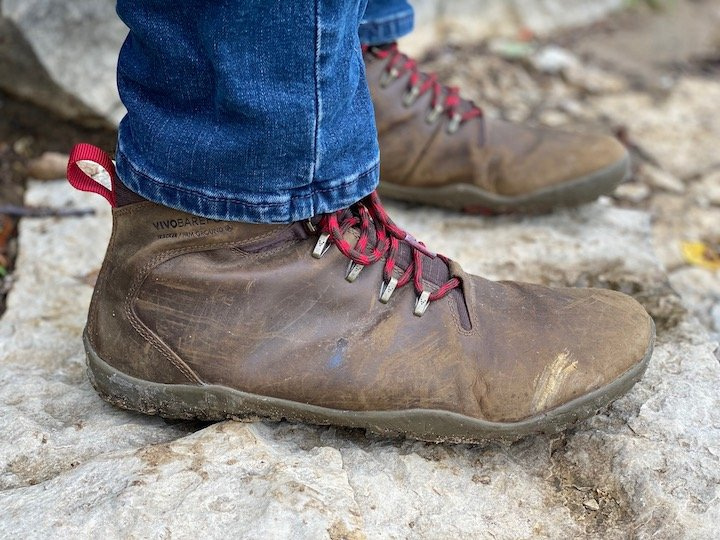A side view of a pair of feet wearing the Vivobarefoot Tracker barefoot hiking boot, standing on rock outdoors