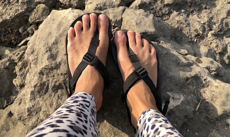 The black Shamma Barefoot Running Warrior Sandals close up on feet top down view in nature, with rocks