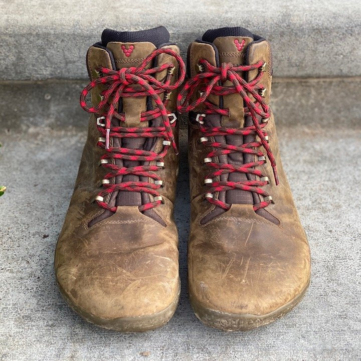 a close up of a pair of vivobarefoot trackers in brown sitting on concrete for the best barefoot minimalist hiking boots review