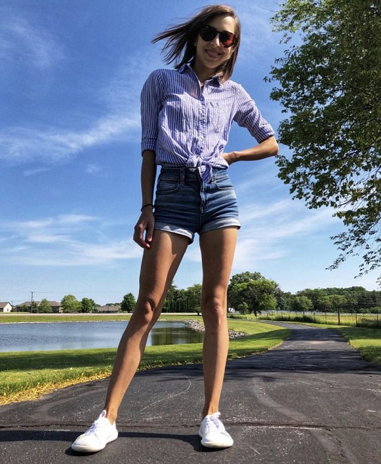 A full body image of a woman posing in white leather sneakers from Belenka barefoot outside with a blue sky and wind in her hair