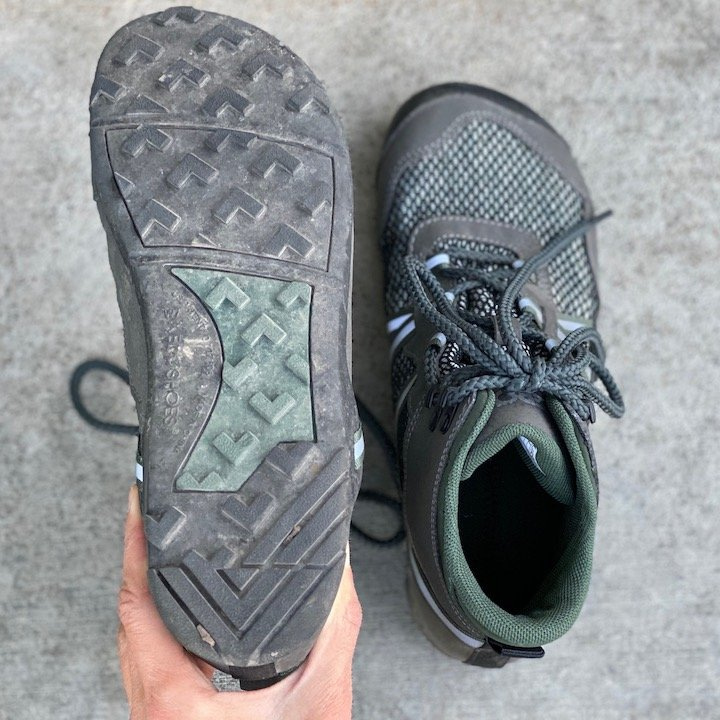 a close up of a pair of Xero shoes vegan Xcursion green sitting on concrete with the outsoles visible for the best barefoot minimalist hiking boots review