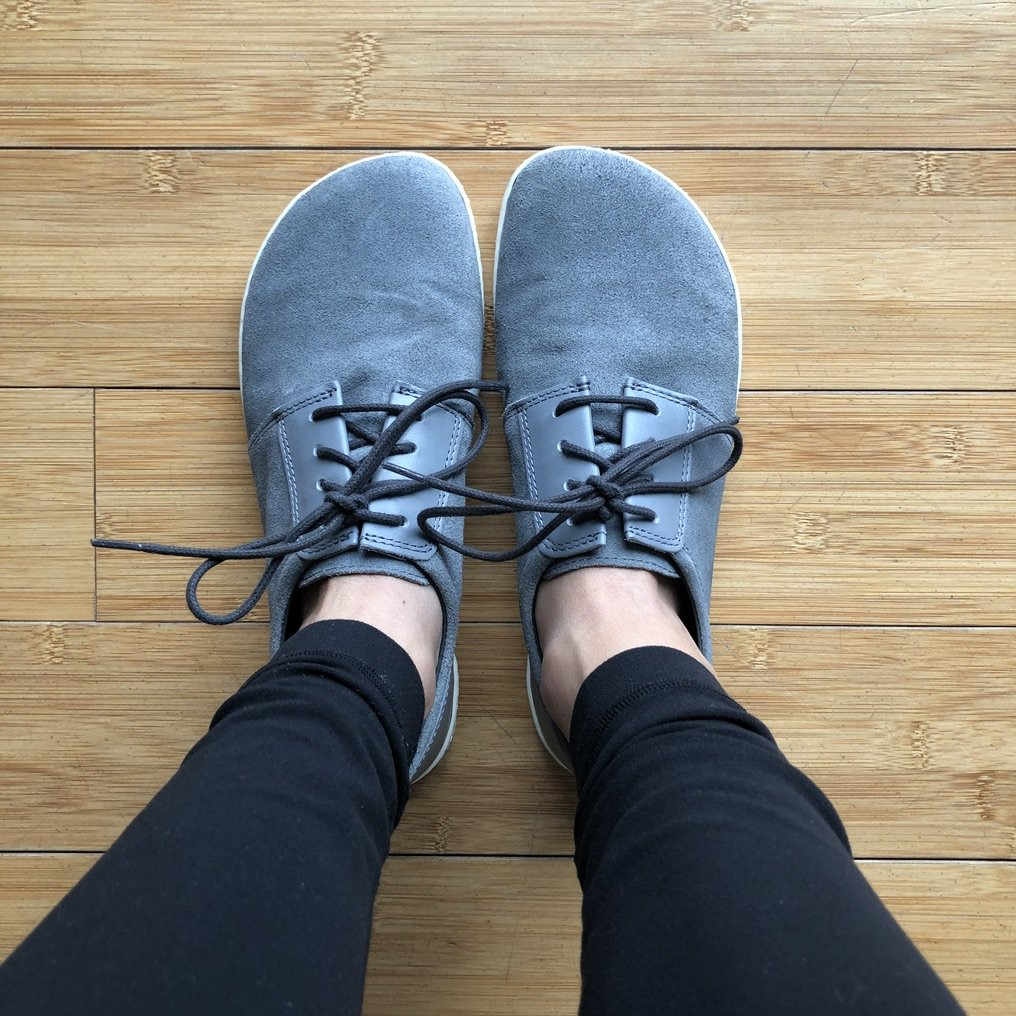 top down view of feet Zaqq Piquant sneakers in grey on wood floor