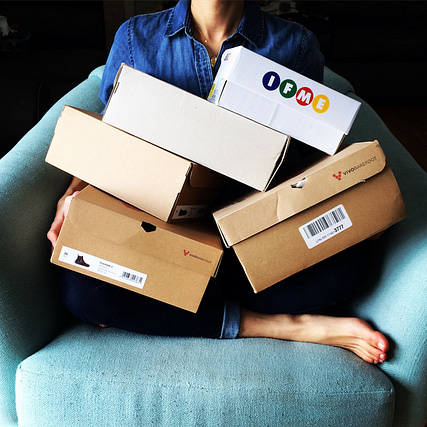 An image of a woman holding a pile of shoe boxes showing the black friday, cyber monday sales, discounts, and coupon codes on barefoot shoes and accessories.