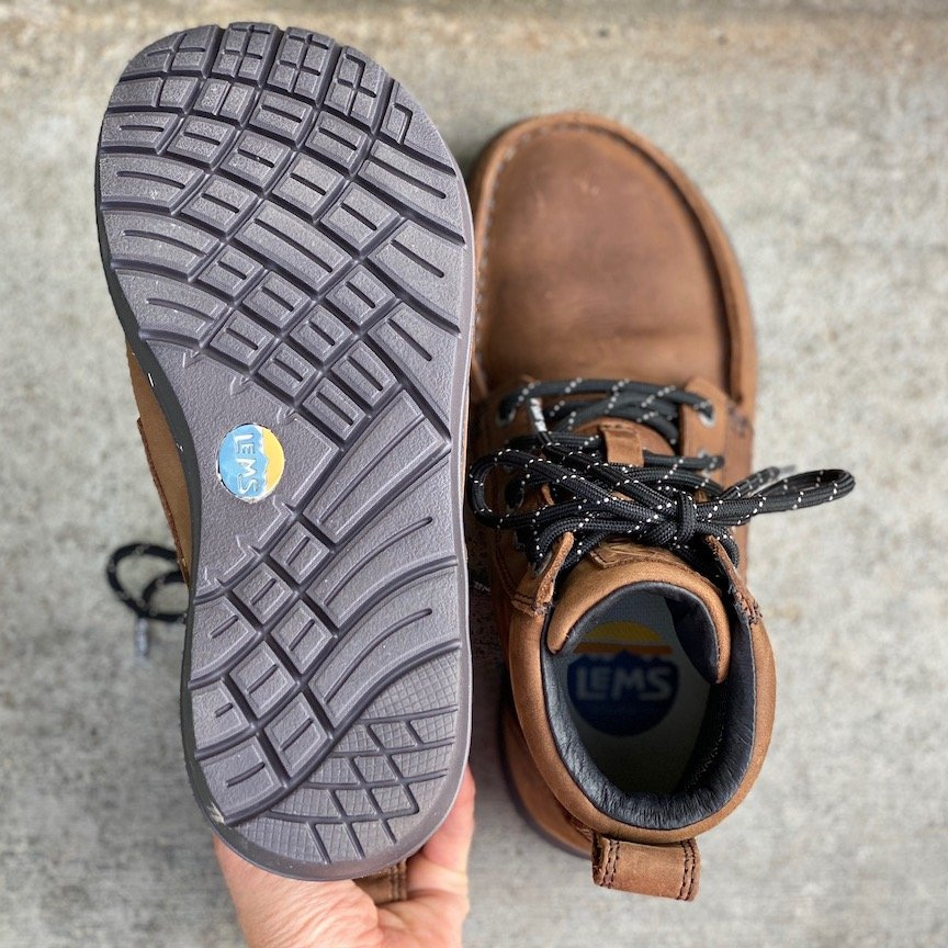 a close up of a pair of lems waterproof boulder sitting on concrete with the outsoles visible for the best barefoot minimalist hiking boots review