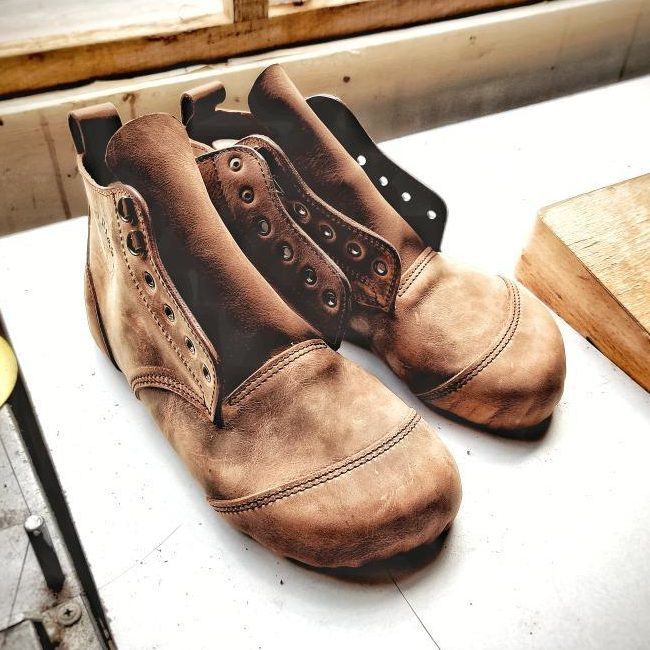 a close up of a pair of gaucho ninja minimalist handmade work boots sitting on the table