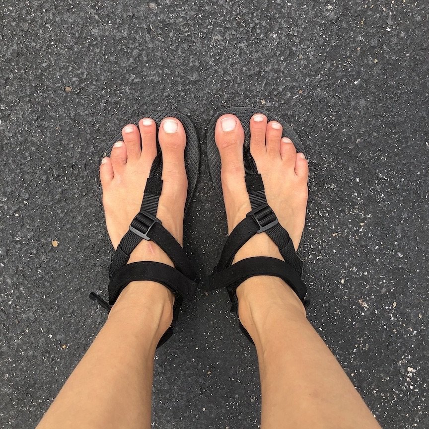 The black Shamma Warrior Sandals shown on feet with the Power Straps on, top down on view on asphalt