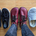 a top down view of a row of vegan barefoot shoes, with a person wearing the middle pair. Show are yellow Mukishoes, Feelgrounds Original, Red Ahinsa boots, Belenka eazy sneakers, and Oesh townie flats