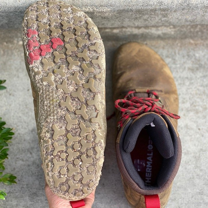 a close up of a pair of vivobarefoot tracker brown sitting on concrete with the outsoles visible for the best barefoot minimalist hiking boots review
