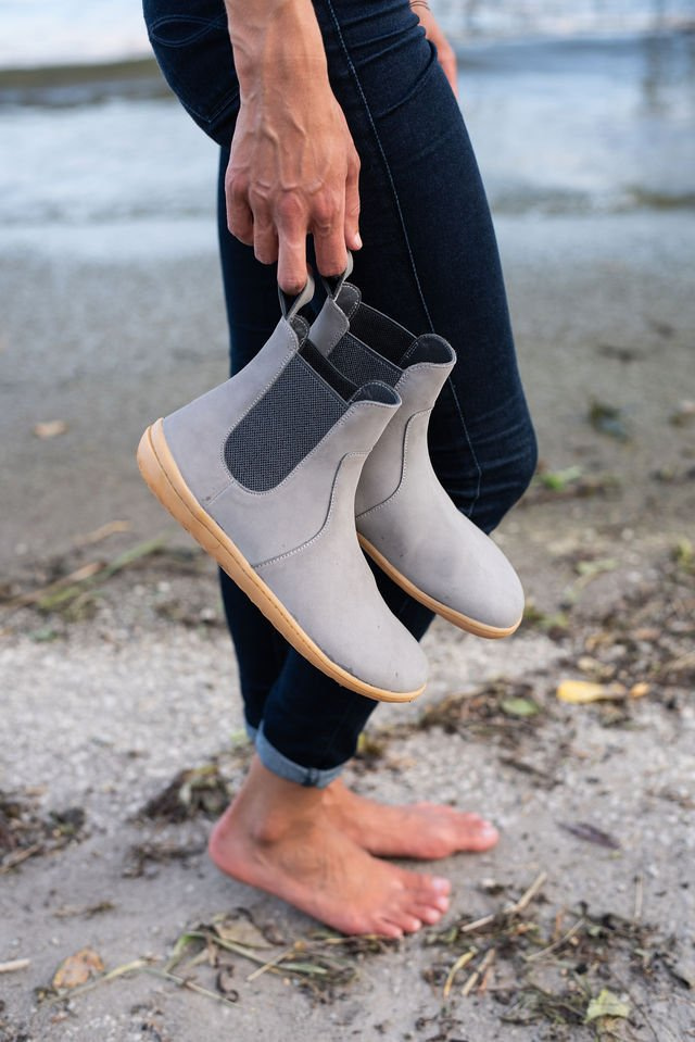 A woman holding a pair of vivobarefoot Fulham Chelsea barefoot boots in zinc grey