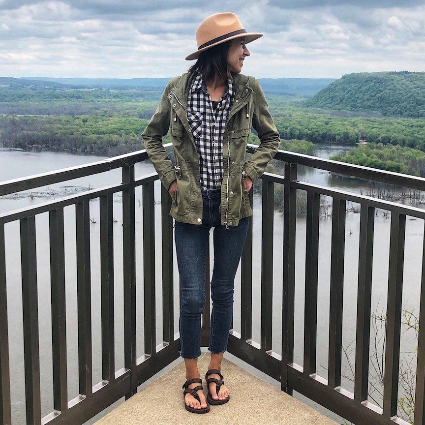 Woman shown standing on an overlook point above a river wearing Shamma Super Goat Barefoot Running Sandals