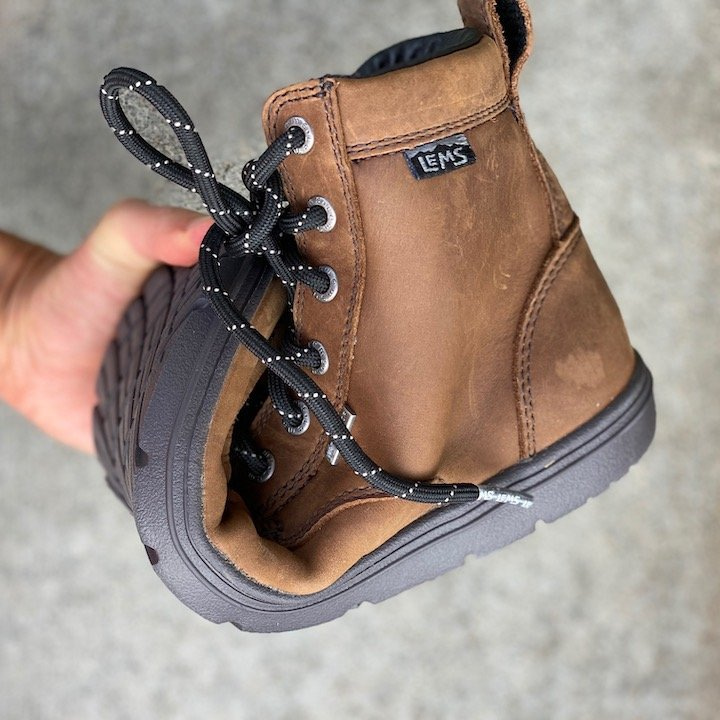 a close up of a hand holding a rolled up lems waterproof boulder boot in brown leather for the best barefoot minimalist hiking boots review
