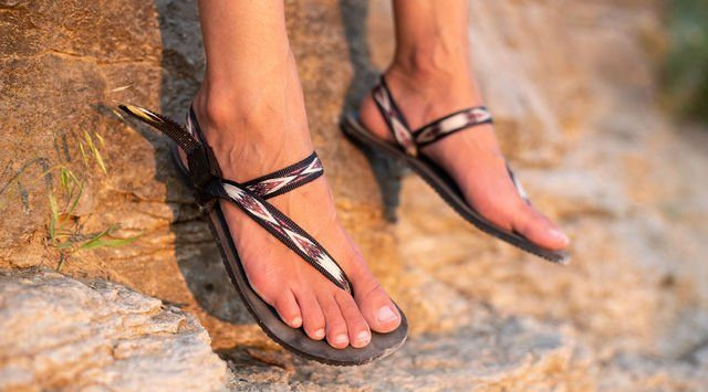 close up of feet dangling in front of rock with earth runners vegan elemental sandals in tribal strap on