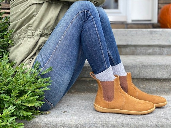 The Vivobarefoot Fulham barefoot chelsea boot review in desert sand tan nubuck, on a woman sitting on the steps. Side view