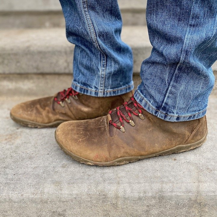 a close up of a pair of feet wearing the Vivobarefoot Tracker barefoot hiking boot