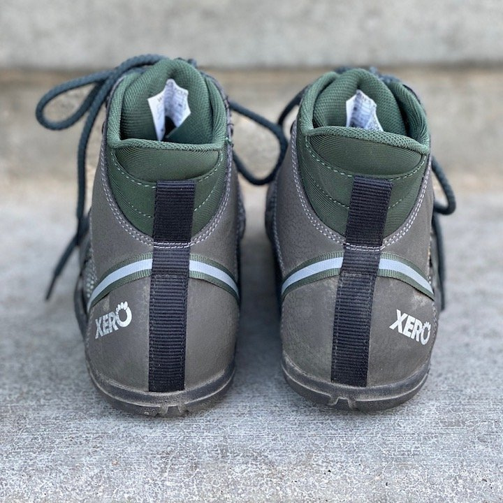 a close up of a pair of Xero shoes vegan Xcursion green sitting on concrete with the heels visible for the best barefoot minimalist hiking boots review