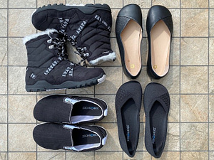 A top down image of 4 pairs of black Xero barefoot shoes sitting on tile. The Alpine waterproof vegan snowboot, the leather Phoenix ballet flat, the knit phoenix, and the hemp vegan Aptos slip on sneaker