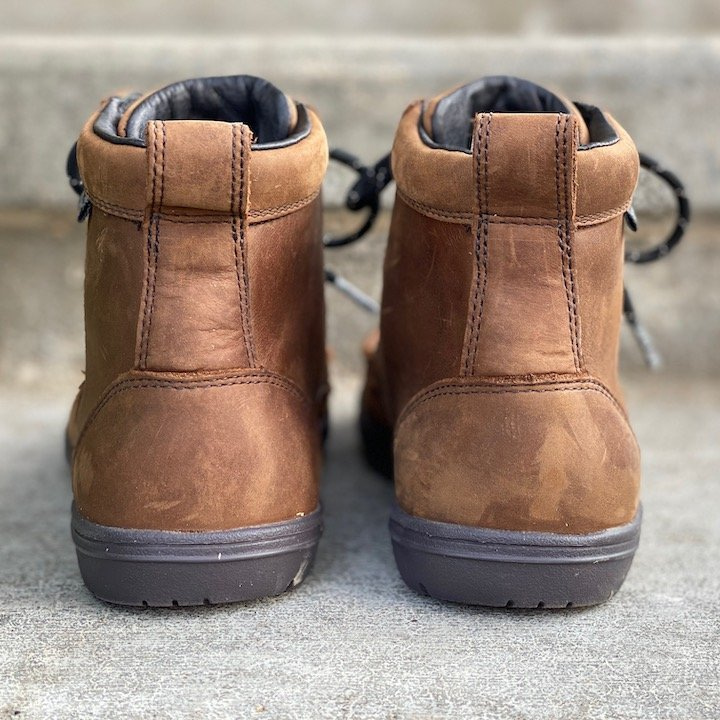 a close up of a pair of lems waterproof boulder brown sitting on concrete with the heels visible for the best barefoot minimalist hiking boots review