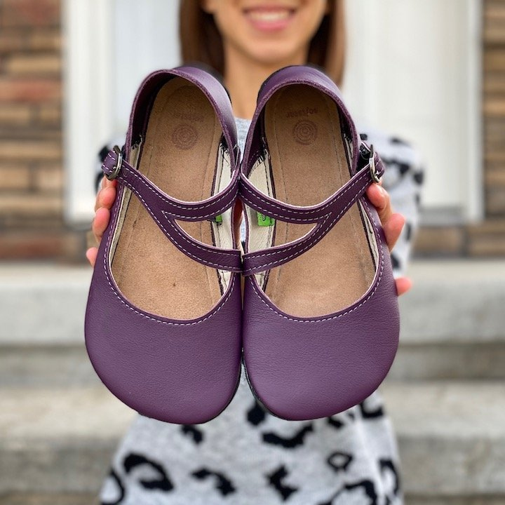 A close up of a woman holding out a pair of Primal Merry Jane barefoot shoes from Softstar