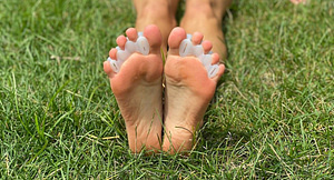 A close up of a pair of bare feet sitting on the grass with only the bottoms visible, wearing Correct Toes spacers