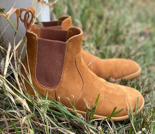 A pair of Vivobarefoot Fulham barefoot chelsea boots review in desert sand tan nubuck sitting on grass next to a white fence post, side view with the elastic panels showing.