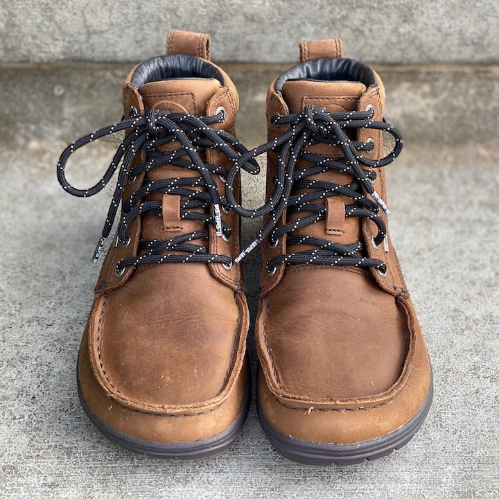 a close up of a pair of lems waterproof boulder boots in brown leather sitting on concrete for the best barefoot minimalist hiking boots review
